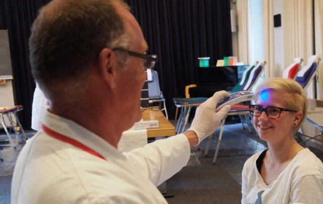 Reinhard Gehring vom Deutschen Roten Kreuz misst kontaktlos die Temperatur an der Stirn von Jana Maiwald, FSP-U. Eine erhöhte Körpertemperatur würde einen ersten Hinweis auf eine mögliche Infektion geben, die zum Ausschluss vom Blutspenden führen würde. (Foto: SMMP/Müller)
